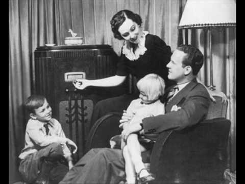 A family gathered around their radio.