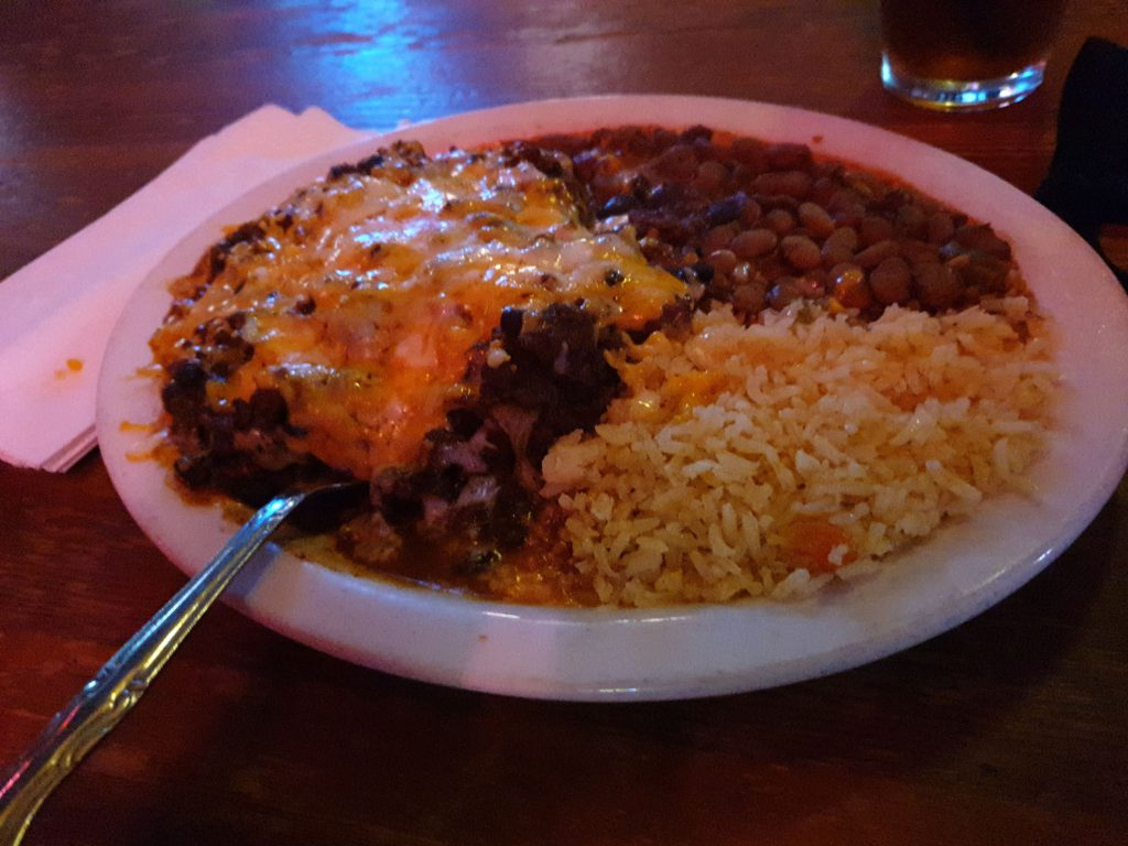 plat of food, melted cheese over chili with food under it along with rice and beans