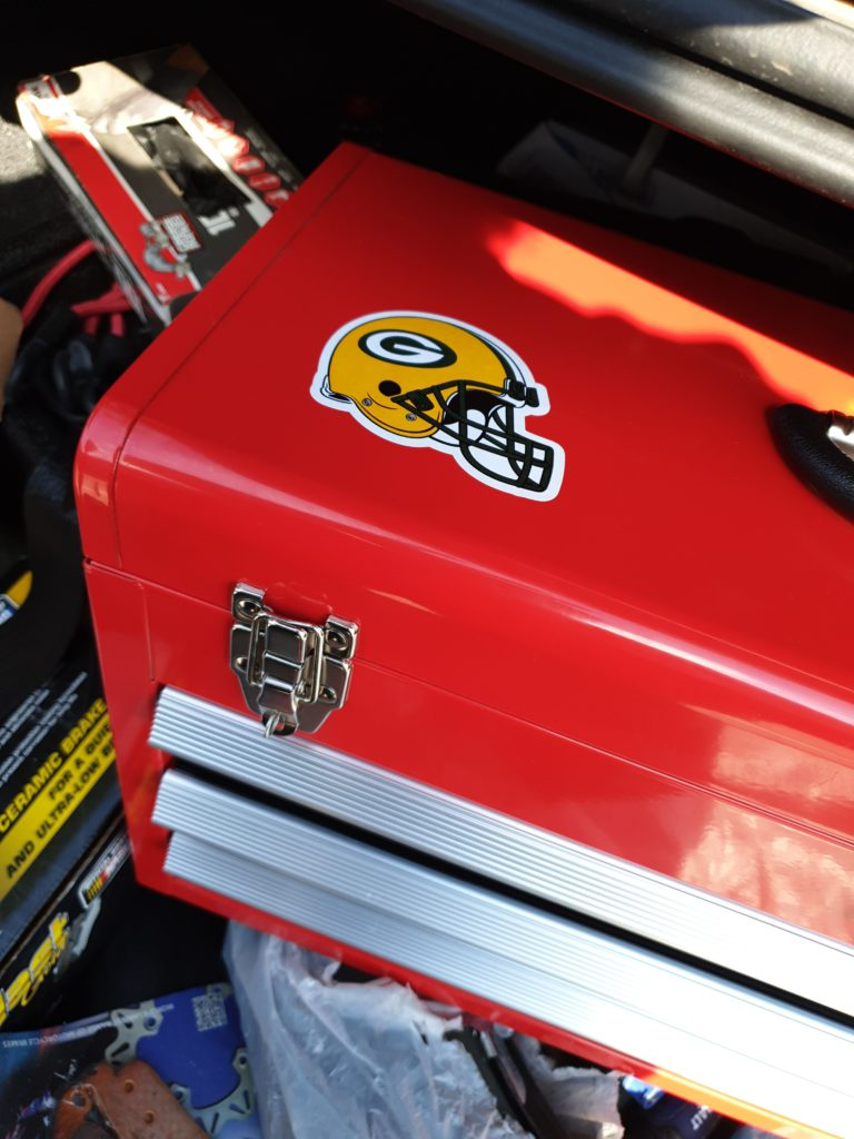 Cropped image of red toolbox with Green Bay Packers NFL Football Team sticker on it.